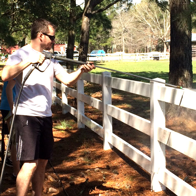 Marcel power washes a fence
