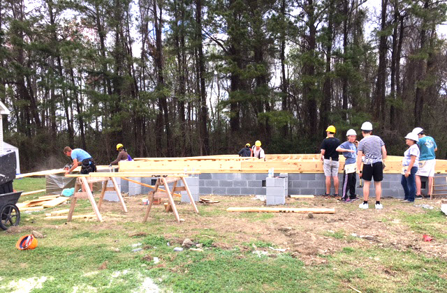 Members of Habitat for Humanity and Hawkes Learning start building on top of the future house's foundation.