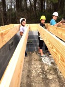 Venessa and Laura have hard hats on and help lay boards on top of the foundation.