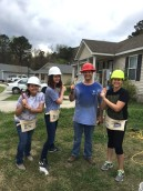 Venessa, Florie, Jeff, and Laura pose on the lawn with hammers in hand.
