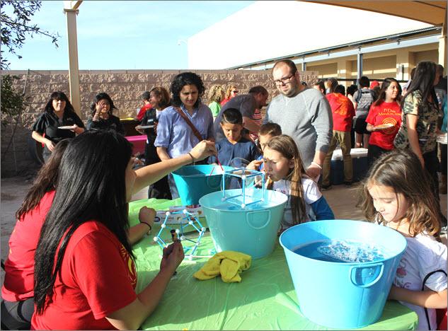 Participants blow into cube-shaped bubble contraptions.