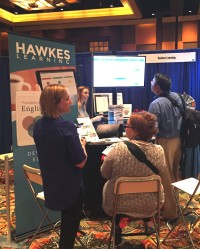 Two Hawkes representatives chat with two instructors in front of the Hawkes Learning booth as the TV monitor displaying the courseware bathes the room in an ethereal fluorescent glow.