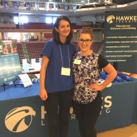 Florie and Megan stand on stage in front of a table with the Hawkes Learning logo.