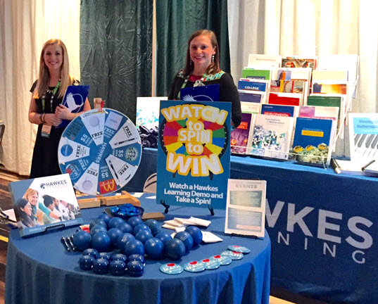 Ashlyn and Liz stand behind a table full of giveaways like yo-yos, buttons, and stress balls, as well as a spinning wheel for prizes.