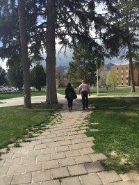 Ashley and Professor Potter walk away from the camera along a wooded path on campus.