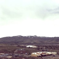 An overcast sky looms over the mountains behind the school buildings.
