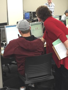A student sits in front of a computer as an instructor leans in to take a closer look at the monitor and provide help.