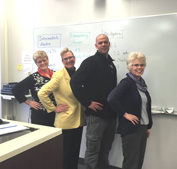 """Instructors standing in front of a classroom white board strike the """"Hawkes Pose"""" by putting their hands on their hips."""