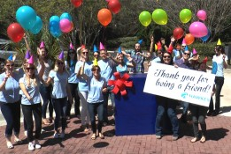 Hawkes employees all dressed in blue hold balloons and wear party hats. Two employees hold up a sign that says thank you for being a friend.
