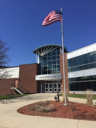 The front entrance to Riverland Community College underneath a perfect blue sky and next to an American flag waving proudly in the breeze.