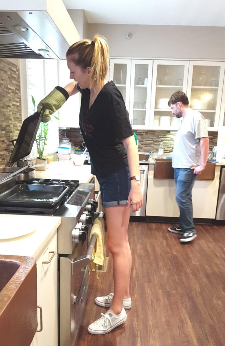 Sarah lifts a sheet pan off the oven.
