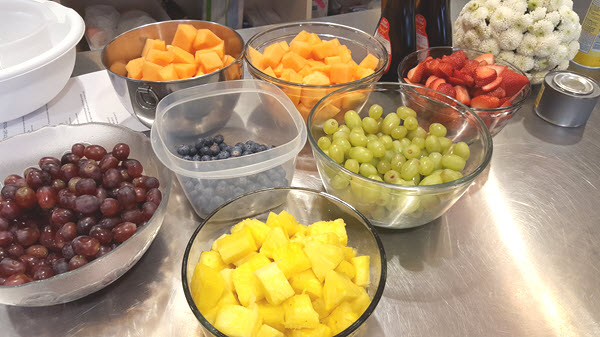 Bowls of fruit, including grapes, blueberries, pineapple pieces, strawberries, and cantaloupe.