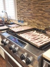 Trays and trays of uncooked bacon sit on the oven and await being cooked and then devoured.