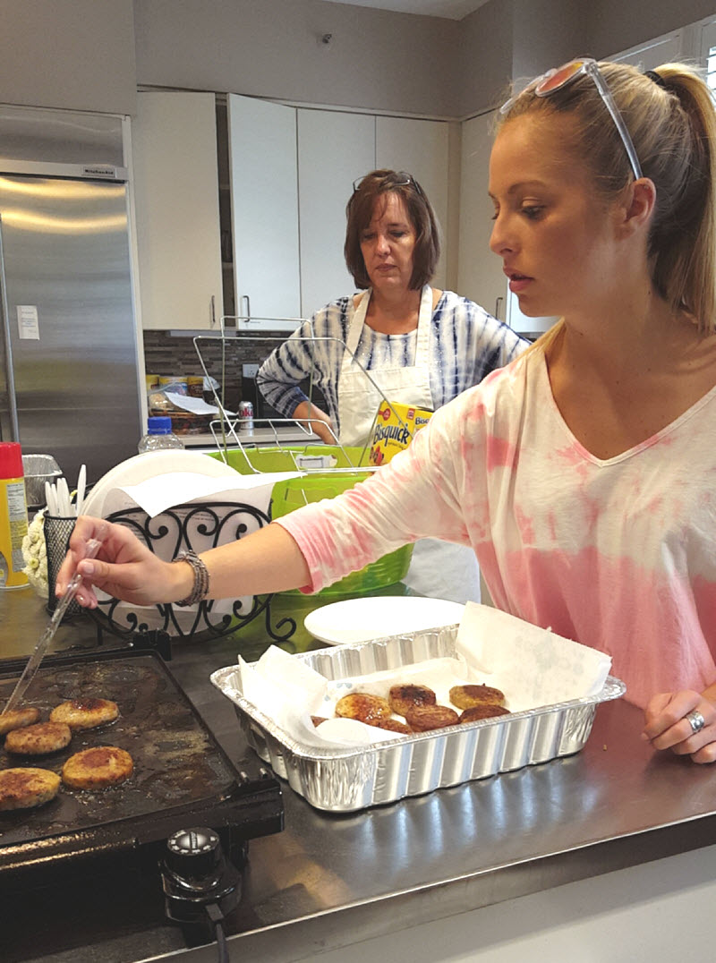 Ashlyn takes the cooked sausage patties from the electric griddle and places them on a paper towel as Lisa looks on and demonstrates more self-restraint than I have when it comes to breakfast foods.