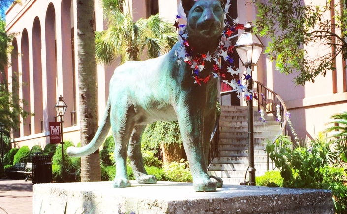 The statue of a cougar at the College of Charleston has a red, white, and blue plastic top hot and star necklace.