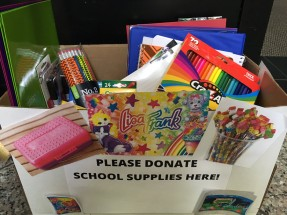 "A box full of folders, binders, pencils, and colored pencils. The box has a sign that says ""Please donate school supplies here."""