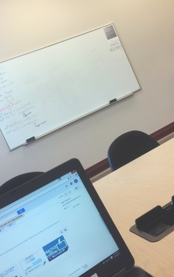 A laptop screen is in the foreground; beyond is a whiteboard with equations written on it.