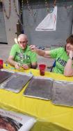 Volunteers hold a flaming dollar bill away from themselves in a fun experiment.