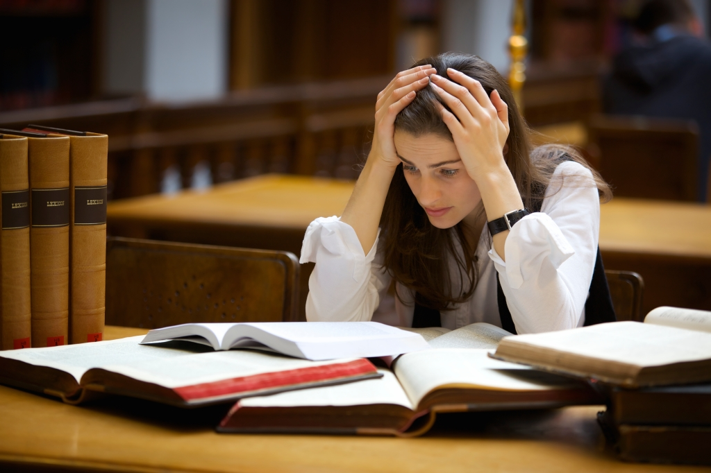 Stressed-out student stares at a pile of books.